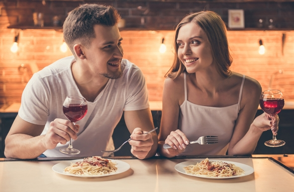 Beautiful couple is talking and smiling while having a romantic dinner together in the kitchen - What Does A Gemini Man Crave From A Woman